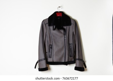 Short sheepskin coat,  grey zipper with a black collar. Fur coat isolated on a white wall background.