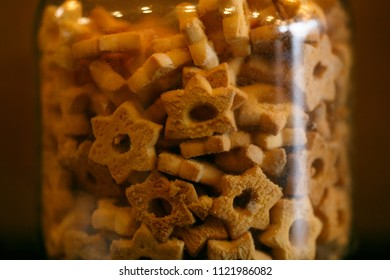 Shortbread cookies in a glass jar. Excellent suitable to a hot drink, perhaps tea or coffee.