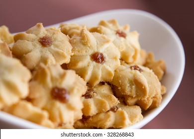 Shortbread cookies with jam in the middle on white plate against brown background