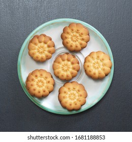 Shortbread cookies in plate on black stone background, top view