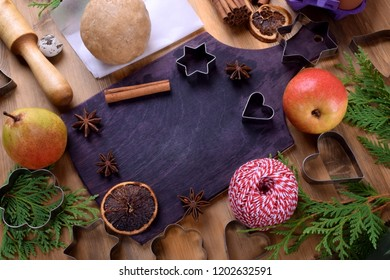 Shortbread dough, pears, spices and baking molds surrounding the black cutting board