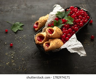 Shortbread envelope cookies with redcurrant jam and ripe redcurrant in a box on a black background.