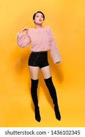 Short-haired girl in fashionable dancing. Young playful female model in stylish fur outfit. Beautiful happy woman having fun dance in studio on yellow
