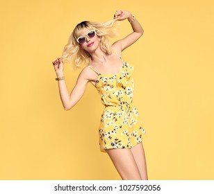 Short-haired girl in Fashionable Sunglasses Dancing. Young Playful female Blond model in Stylish Summer Outfit. Beautiful Happy woman Having Fun dance in Studio on Yellow