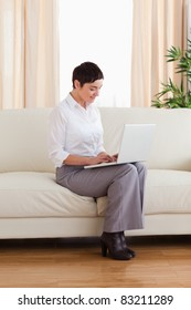 Short-haired woman with a laptop in the living room