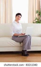 Short-haired woman with a laptop looking into the camera in the living room