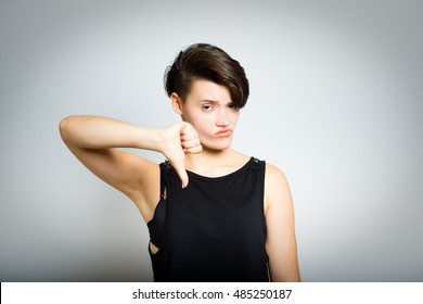 short-haired woman showing a thumb down, do not like it, portrait, isolated on gray background