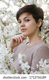 Short-haired young pixie girl in a spring flowered garden.