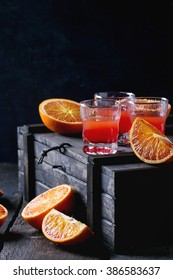 Shorts of alcohol cocktail with Sliced Sicilian Blood oranges and fresh red orange juice, served on black wooden chest over old wooden table. Dark rustic style.
