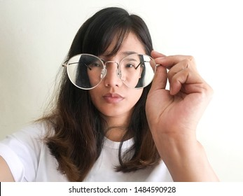Short-sighted woman is holding glasses in hand with white background. symbolic photo for bad vision and refractive error