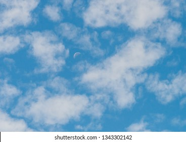 A shot of an abstract formation of clouds surrounding the moon in a blue sky.