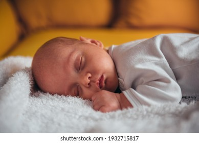 Shot of a adorable baby boy sleeping on a yellow sofa at home