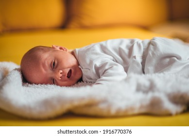 Shot of a adorable little baby boy yawning while lying on a bed at home