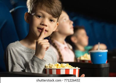 Shot of an adorable little boy shushing to the camera asking for silence while watching a movie at the cinema popcorn snack quiet annoying annoyed gesture leisure entertainment attention children