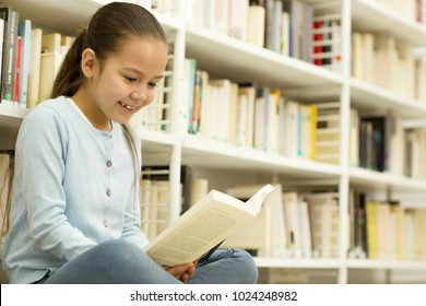 Shot of an adorable little happy Asian girl smiling joyfully reading a book sitting near bookshelves at the library or bookstore copyspace hobby leisure lifestyle education learning homework studying.