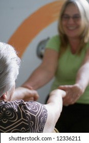 A shot of an adult child help her elderly mother do stretches.