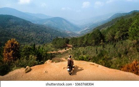 Shot of adventurer enjoy touring motorbike stopped by a cliff viewpoint on mountain peak with pine forest in Vietnam