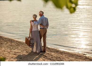 Shot of an affectionate senior couple going on a picnic at the riverbank. Back shot.