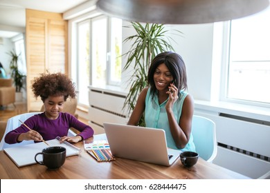 Shot of african american woman working while the daughter is drawing at home.