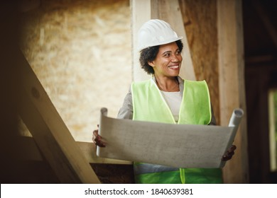 Shot of an African female architect checking plans at the construction site of a new wooden house. She is wearing protective workwear and white helmet.