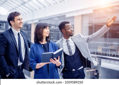 shot of afroamerican estate agent with potential clients inside an empty office space