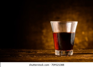 Shot of Alcoholic Bitter Liquor on Wooden Surface