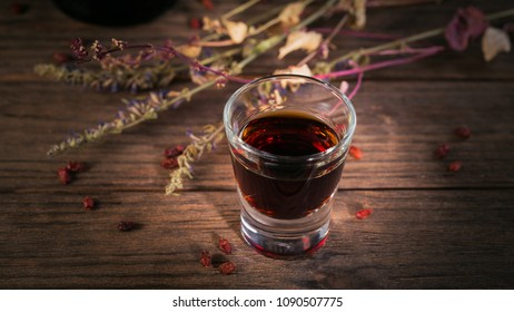 Shot of alcoholic drink on dark wooden background. Herbal bitter liqueur with different natural ingredients.