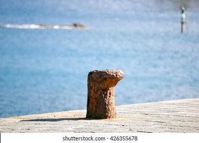 A shot of an alod and rusty ship bollard in a dock