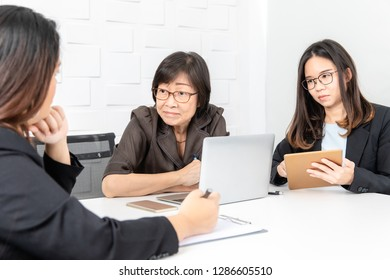 Shot of Asian, senior businesswoman with laptop, and two young staffs sitting in board room in office, on serious discussion and consideration about reviewing and setting new strategic planning