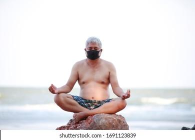 Shot Asian senior old man on the beach doing yoga wearing mask for protect against infection with influenza virus or coronavirus - corona virus - covid19 or civid-19. protection mask virus concept