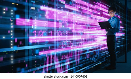 Shot of Asian IT Specialist Using Laptop in Data Center Full of Rack Servers. Concept of High Speed Internet with Pink Neon Visualization Projection of Binary Data Transfer - Shutterstock ID 1440907601