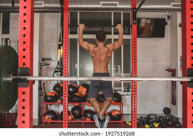 Shot of an athlete with a bare torso. An athletic man pulls himself up on the bar. In the frame of a sports hall with various balls, barbells and dumbbells