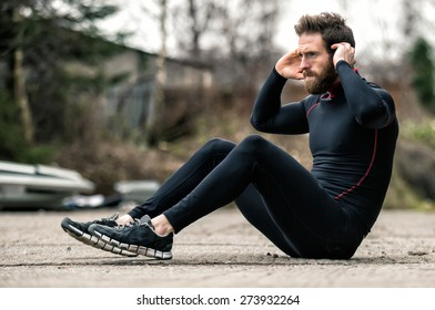A shot of an athlete doing sit-ups outside