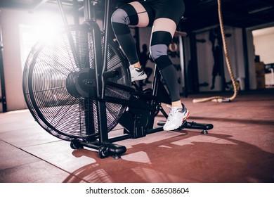Shot of athlete woman exercising on assault air bike.