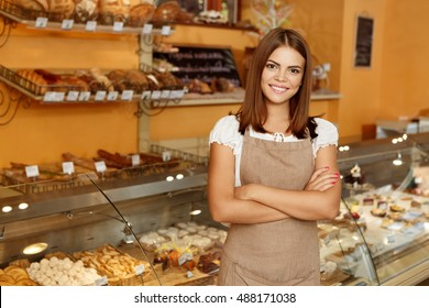 Shot of an attractive cheerful female baker smiling to the camera standing near the showcase copyspace