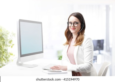 Shot of an attractive customer support agent sitting at her workplace and chatting online.