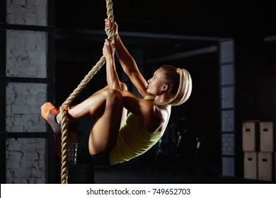 Shot of an attractive female crossfit athlete climbing a rope at the gym. Beautiful woman rope climbing at the crossfit box motivation positivity health concentration agility active living Battle rope