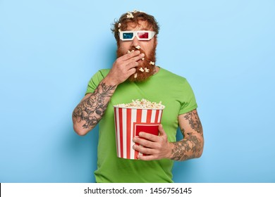 Shot of attractive ginger guy swallows fresh popcorn in cinema while watches exciting movie, wears three dimension glasses and casual green t shirt, all attention at screen, being attentive spectator