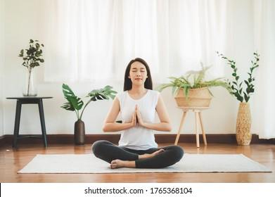Aufnahme einer attraktiven, gesunden asiatischen Frau, die zu Hause Yoga-Meditation macht