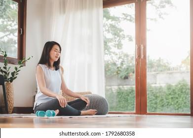 Aufnahme einer attraktiven, gesunden asiatischen Frau, die Meditation zu Hause im Wohnzimmer