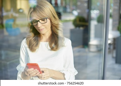 Shot of an attractive mature woman standing behind a glass window while using her mobile phone and text messaging.