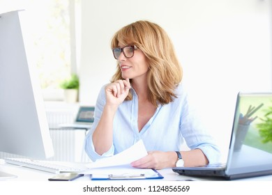 Shot of an attractive middle aged businesswoman working on computer and laptop at office desk.