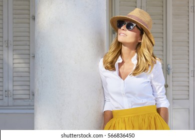 Shot of an attractive middle aged woman wearing sunglasses and straw hat while standing at balcony and enjoying sunshine in the summer.