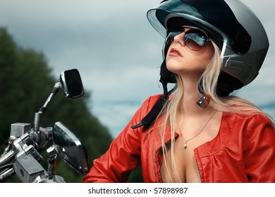 Shot of an attractive woman biker posing near her motorcycle.