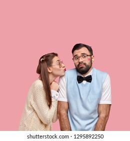 Shot of attractive woman in old style clothes, gives kiss to clumsy boyfriend expresses love and care pose together against pink background. Bearded man feels awkward during first date with girlfriend