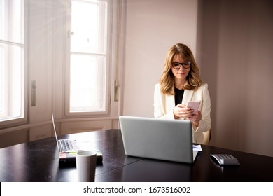 Shot of attractive woman sitting at desk behind her laptop and text messaging while working from home.