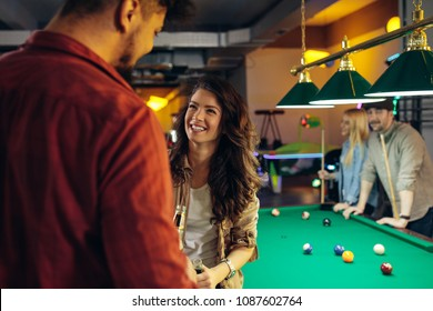 Shot of an attractive young couple drinking beer and talking during a game of billiard
