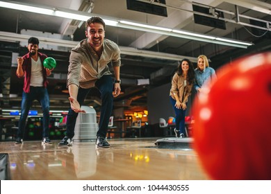 Shot of an attractive young man throwing the bowling ball
