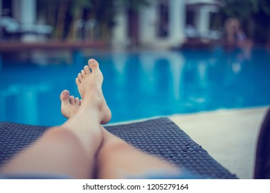 Shot of an attractive young woman relaxing near pool. Legs and midriff. (soft focus)