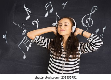A shot of attractive young woman standing in front of a blackboard with musical notes drawn on and listening to music on headphones